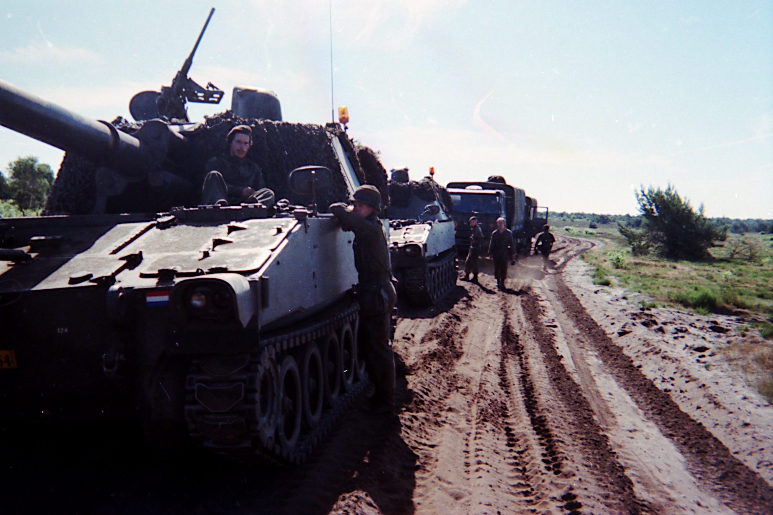 A row of M109 howitzers and trucks waiting to move on, while conscripts are milling about